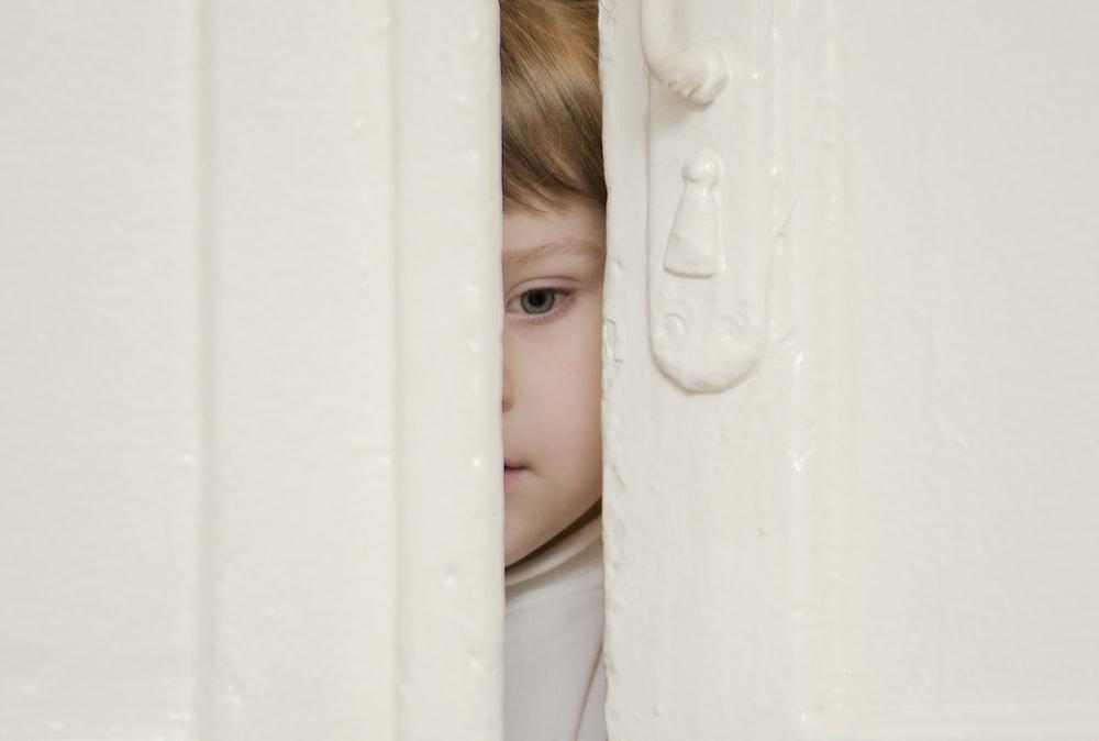 boy looking behind door