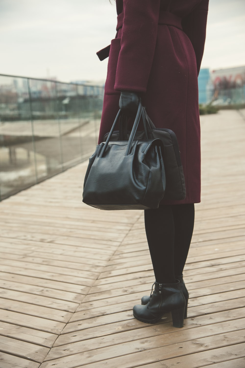 woman standing while holding black bags