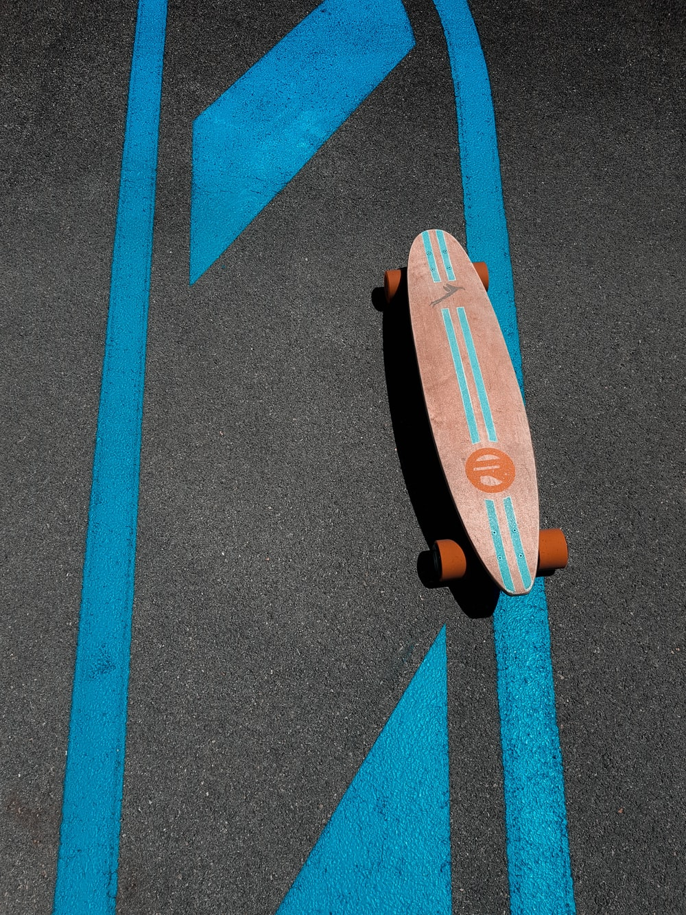 brown and orange skateboard on gray concrete road