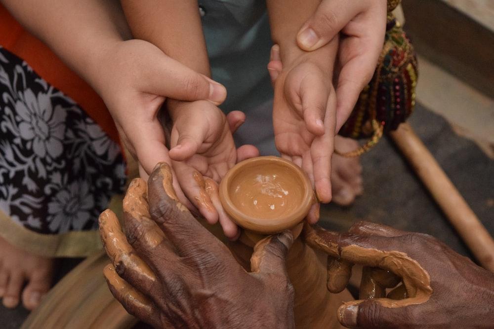 woman holding child's hand towards jar