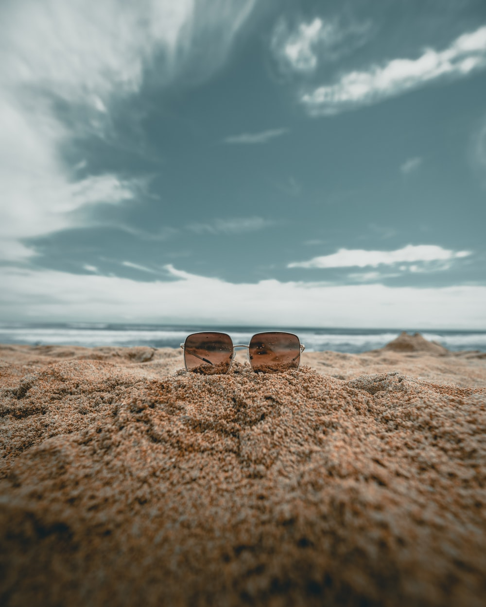 brown lens sunglasses on sand in low angle photography photography