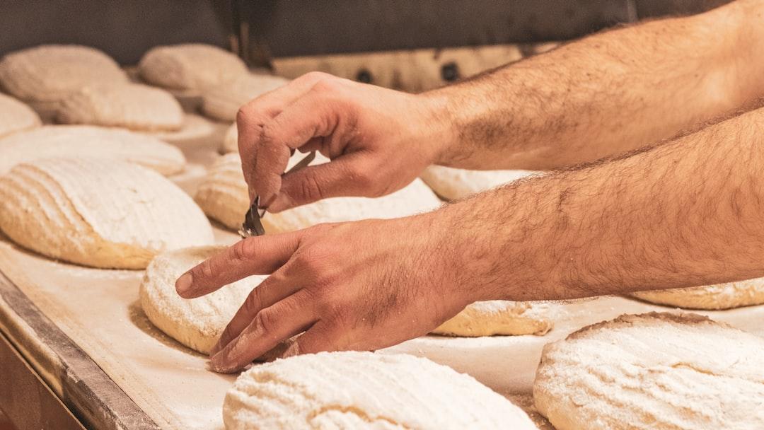baker scoring bread in an organic sourdough bakery
