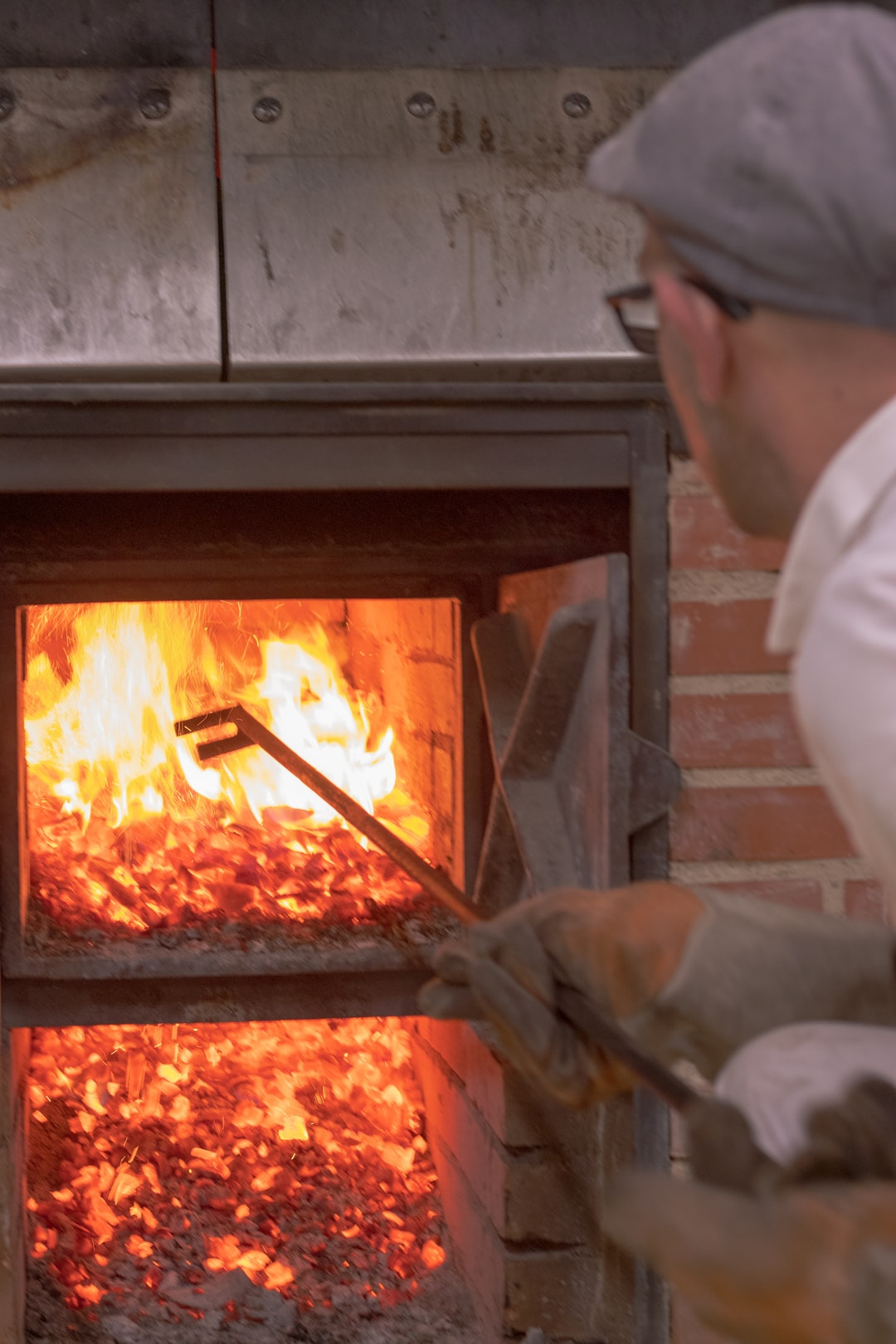 baker fueling his woodfire oven