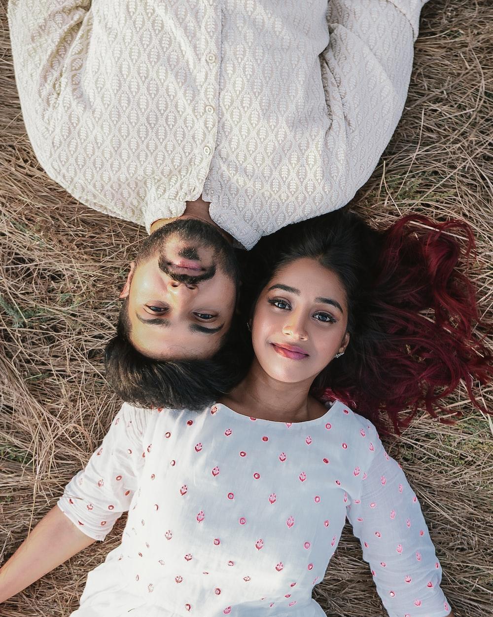 high-angle photography of woman and man lying on brown grass