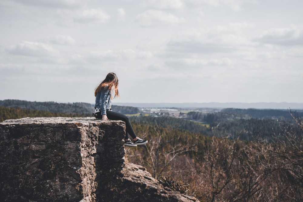 woman sitting on cliff's edge overlooking forest during daytime