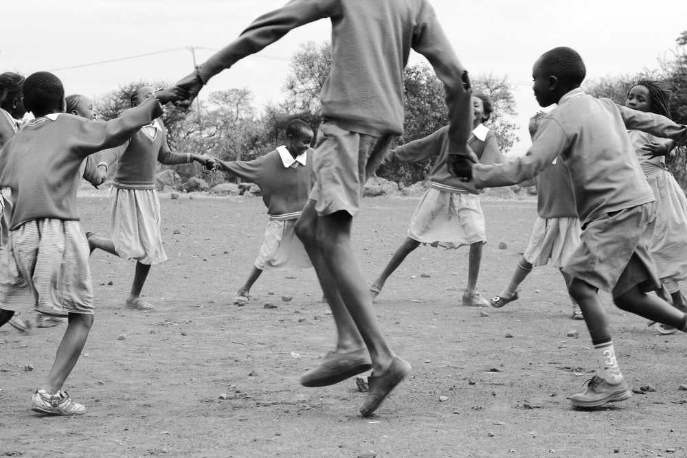 grayscale photography of people playing outside