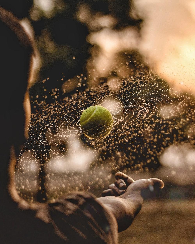 boy playing green tennis ball