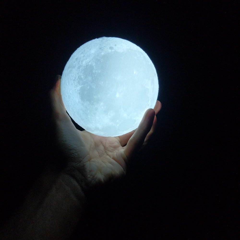 person holding glow-in-the-dark ball