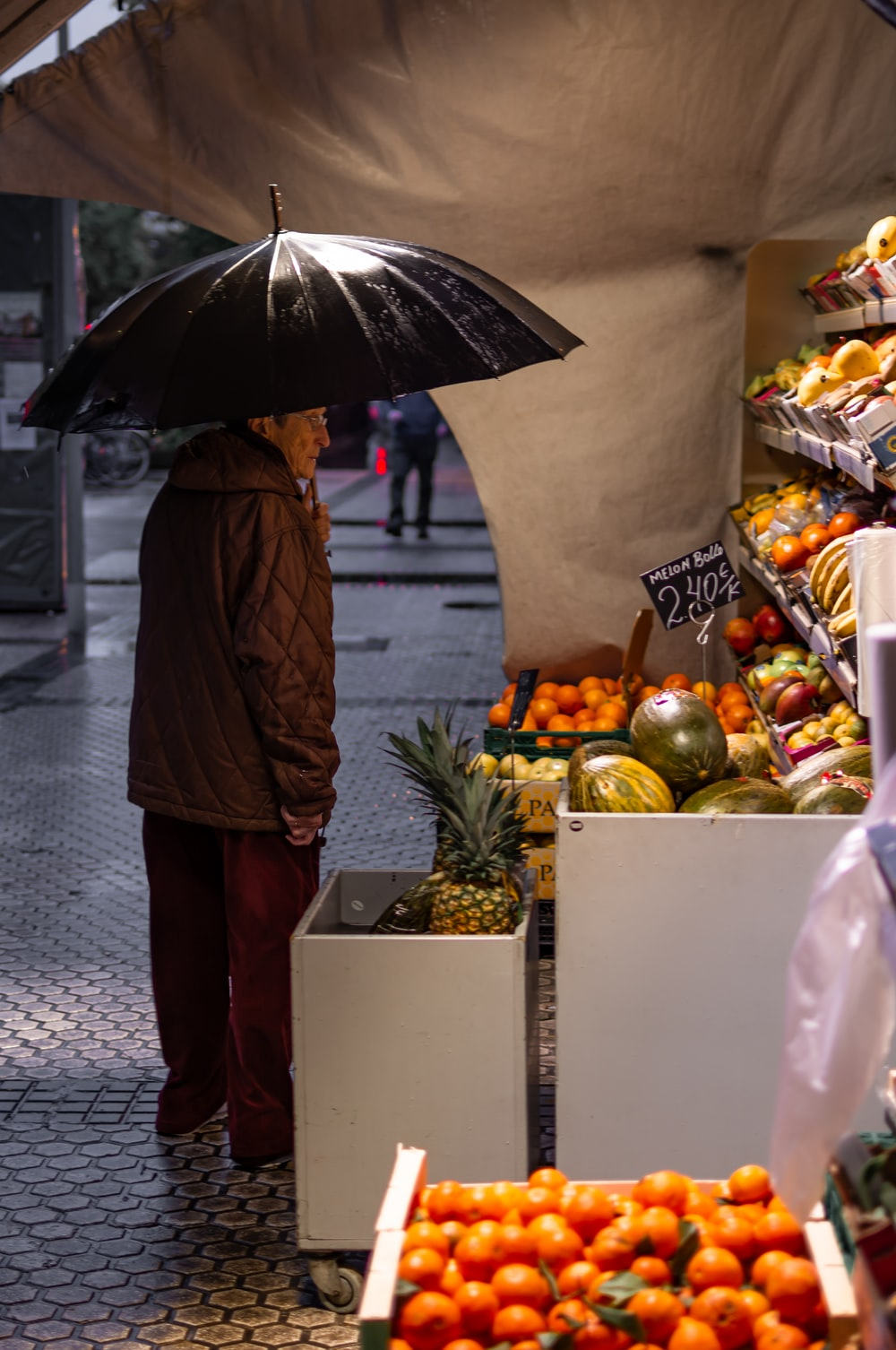 man standing in front fruit stand while holding black umbrella