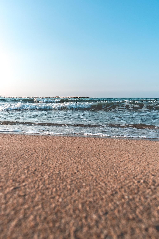 brown sand beside seashore