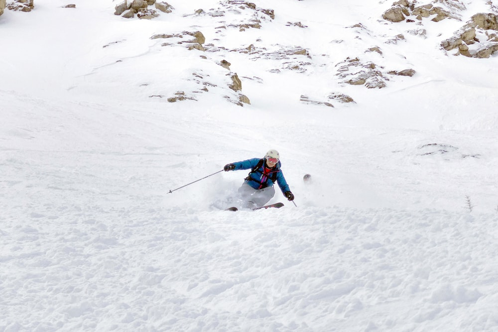 time lapse photography of man skiiing on snowfield