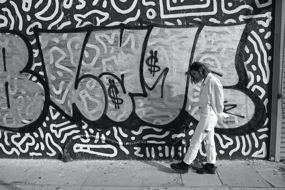 woman walking beside wall