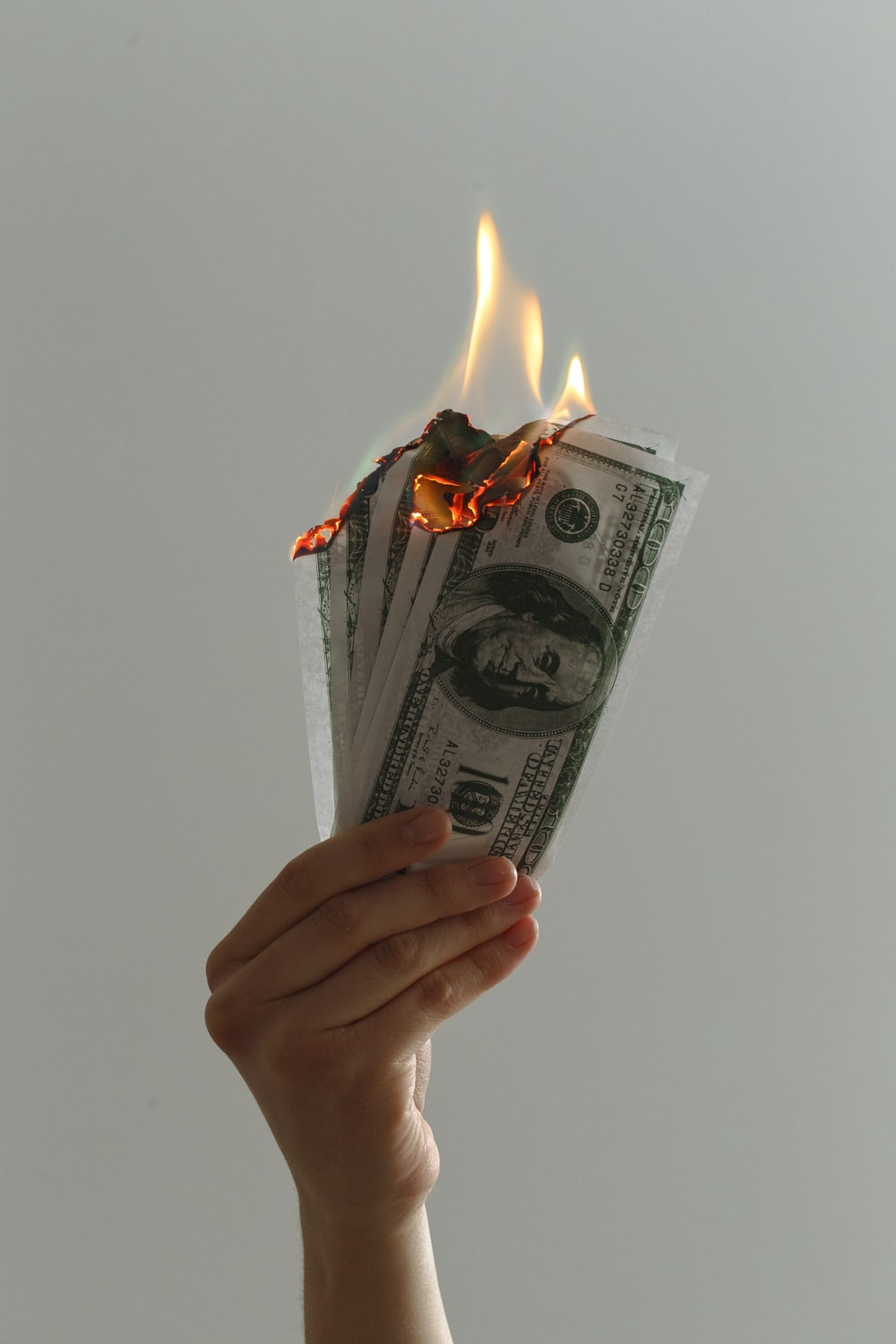 time lapse photography of several burning US dollar banknotes