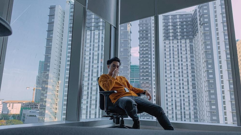 man sitting on chair near glass window