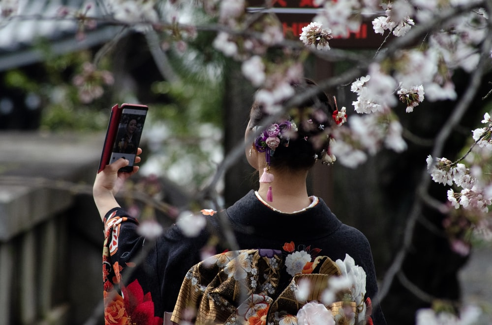 woman using Android smartphone outdoor during daytime