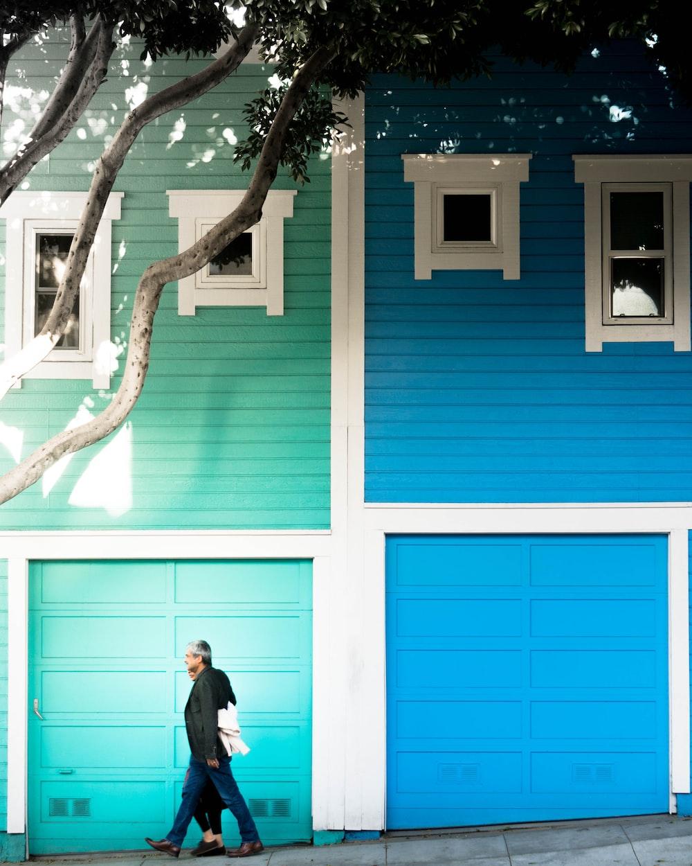 man wearing jacket walking beside blue house