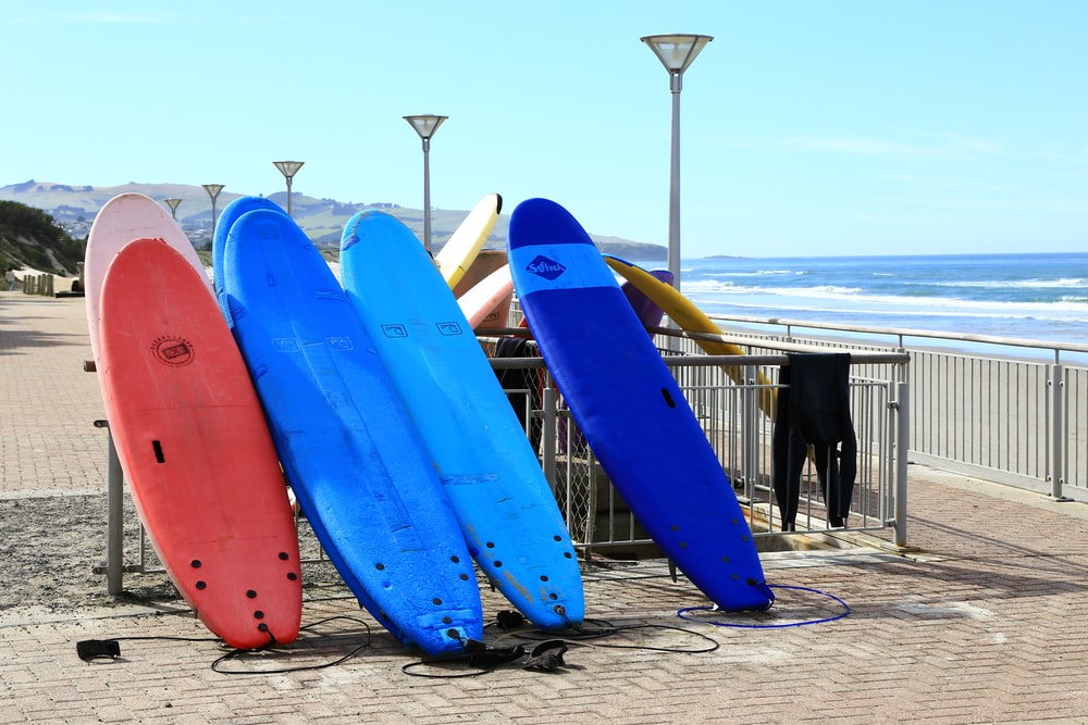 assorted-color surfboards leaning on metal rail