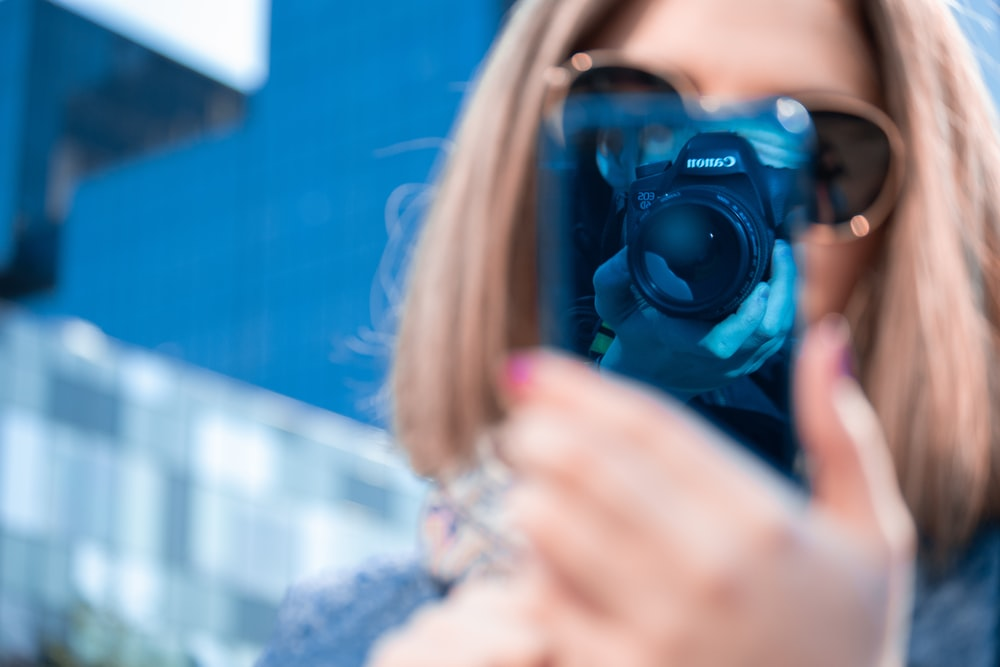 woman taking picture of her smartphone