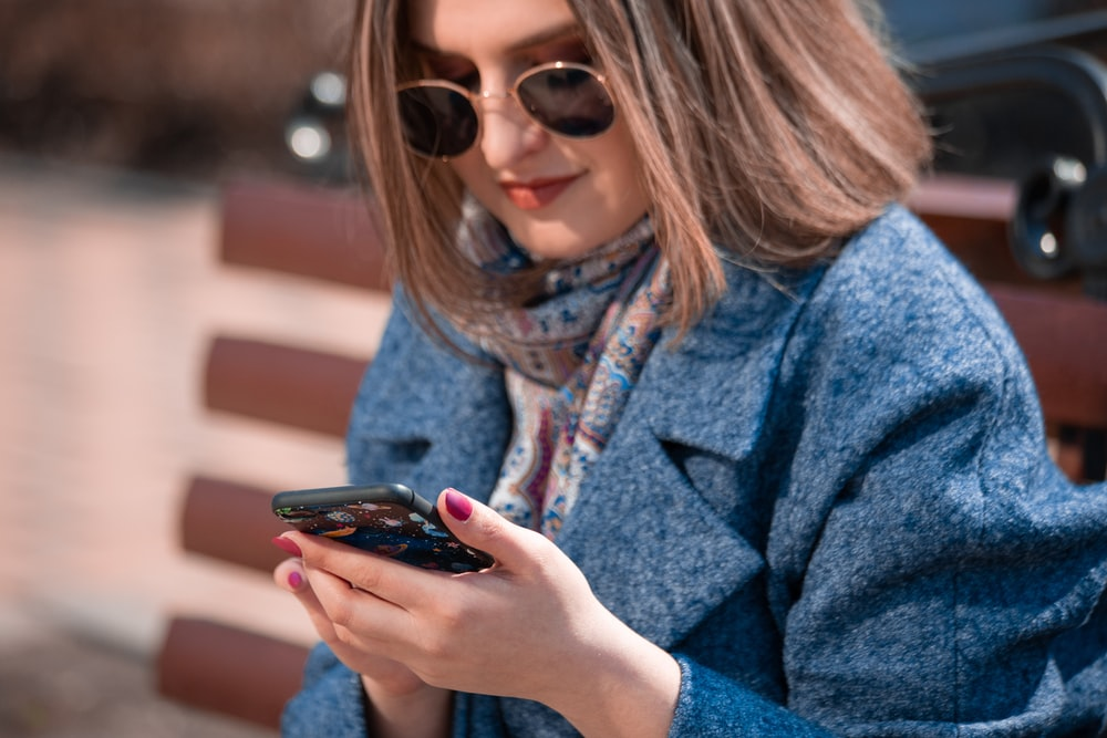 woman in blue coat using smartphone