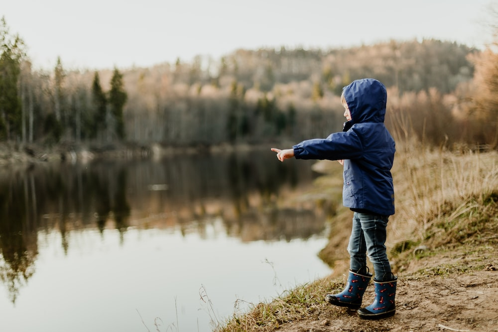 toddler wearing blue jacket pointing the river
