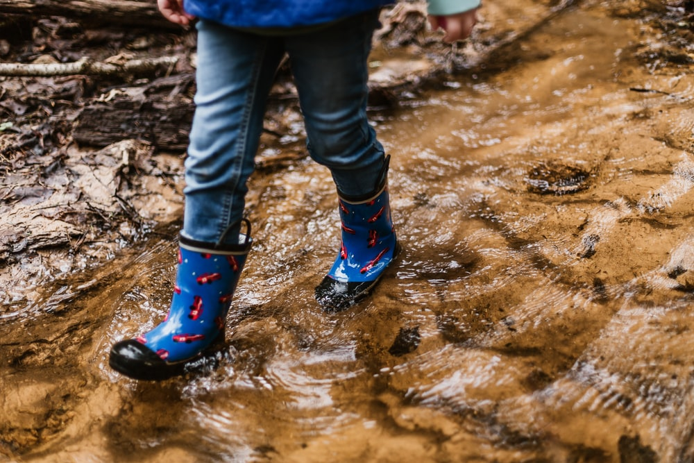 person wearing blue-and-red rain boots