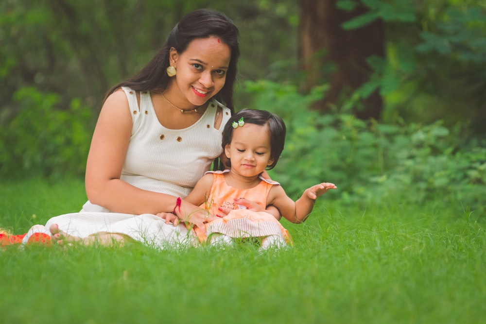 woman wearing white sleeveless dress sitting on grass field with toddler