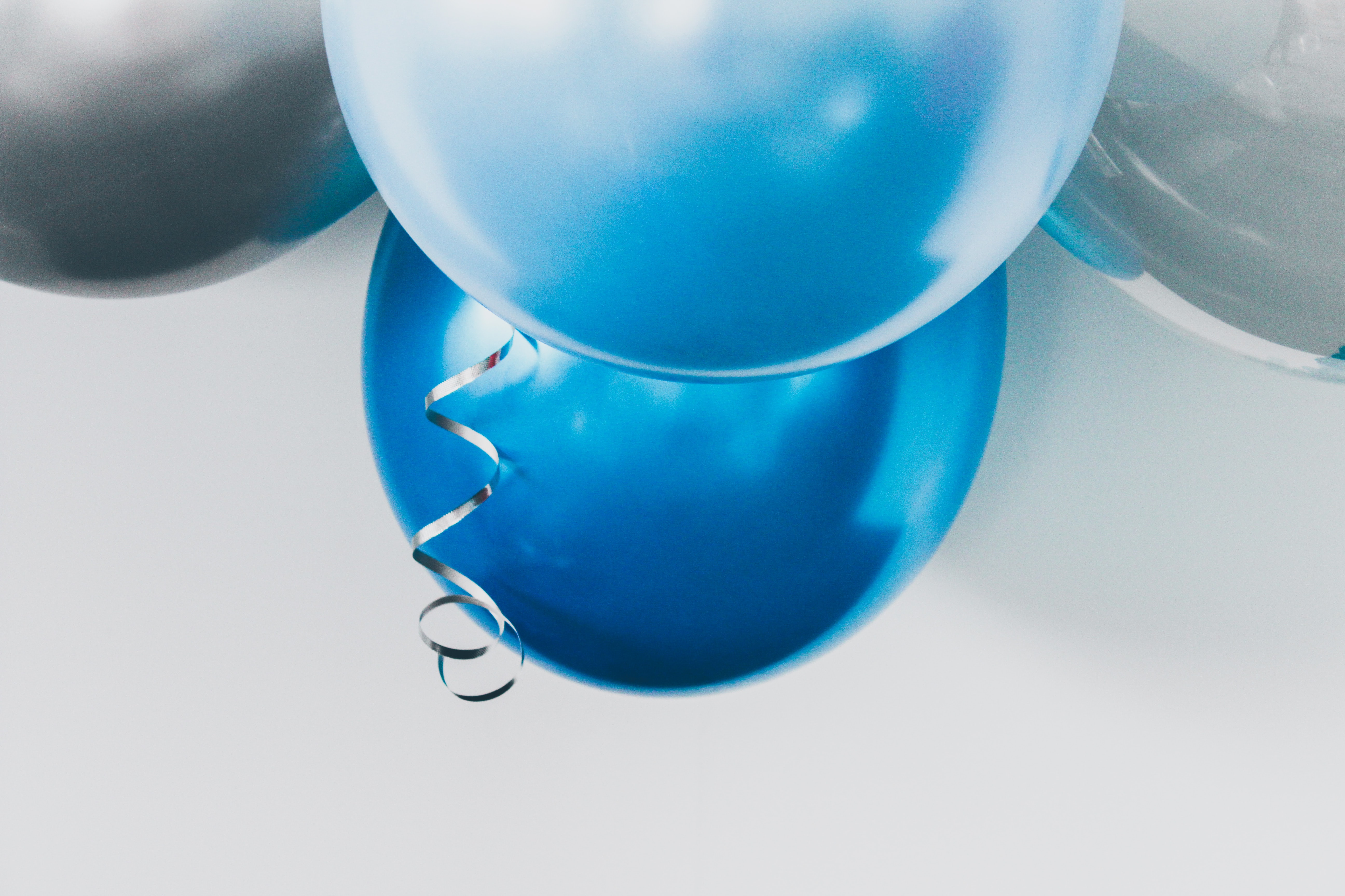 four gray, blue, and white balloons hanged on wall
