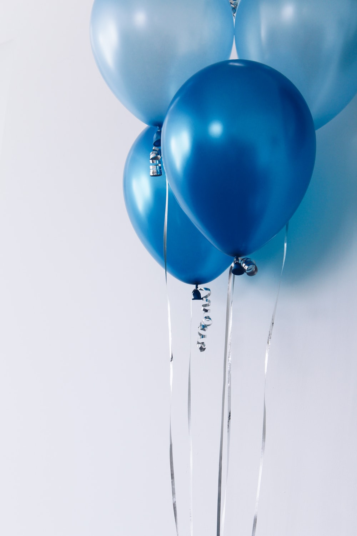 four blue balloons near white wall