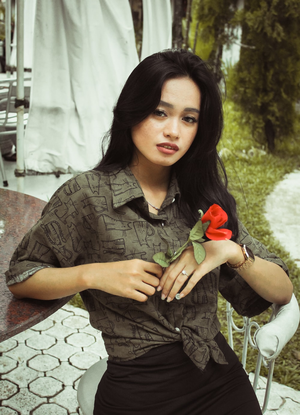 woman sitting beside round brown wooden table holding faux red flower during daytime