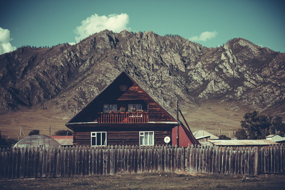 red wooden house with gray wooden fence near mountain under white skies