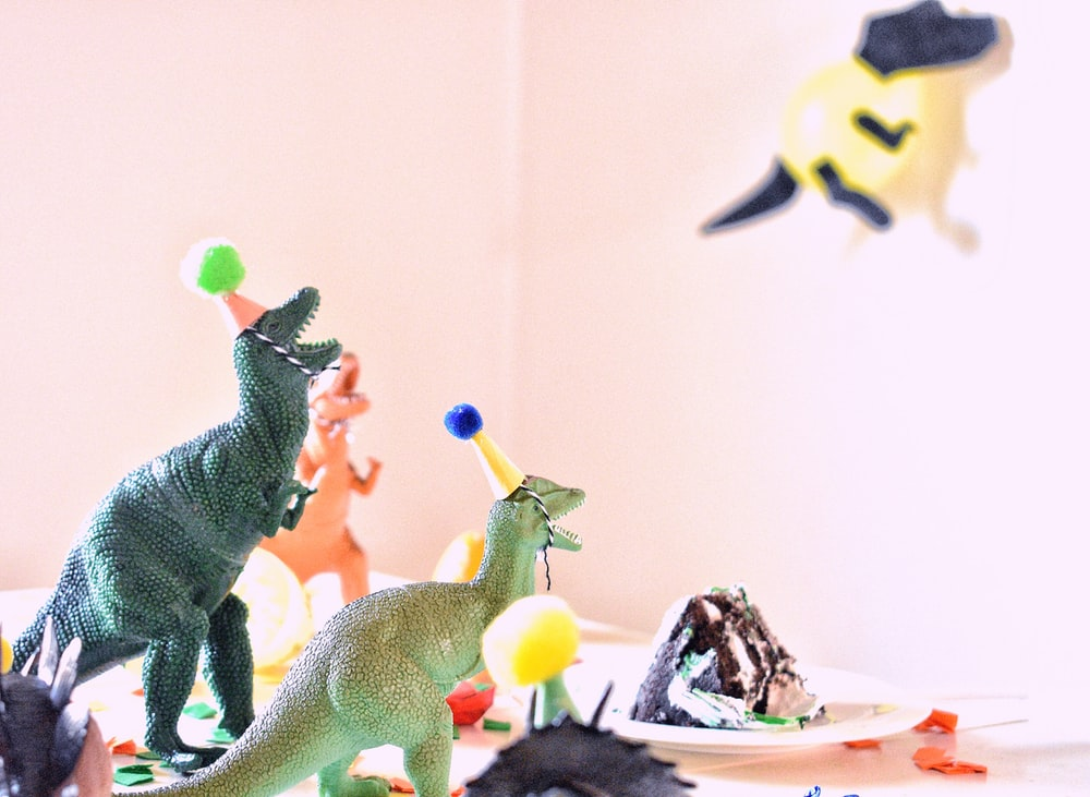 assorted-color dinosaur toys near slice cake on white table