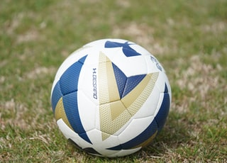 white and blue Under Armour soccer ball on green field