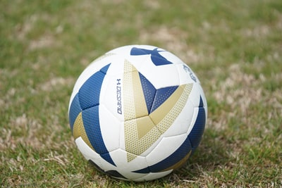 white and blue under armour soccer ball on green field team sport zoom background
