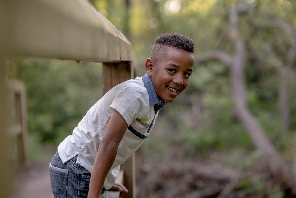 boy holding railing during daytime