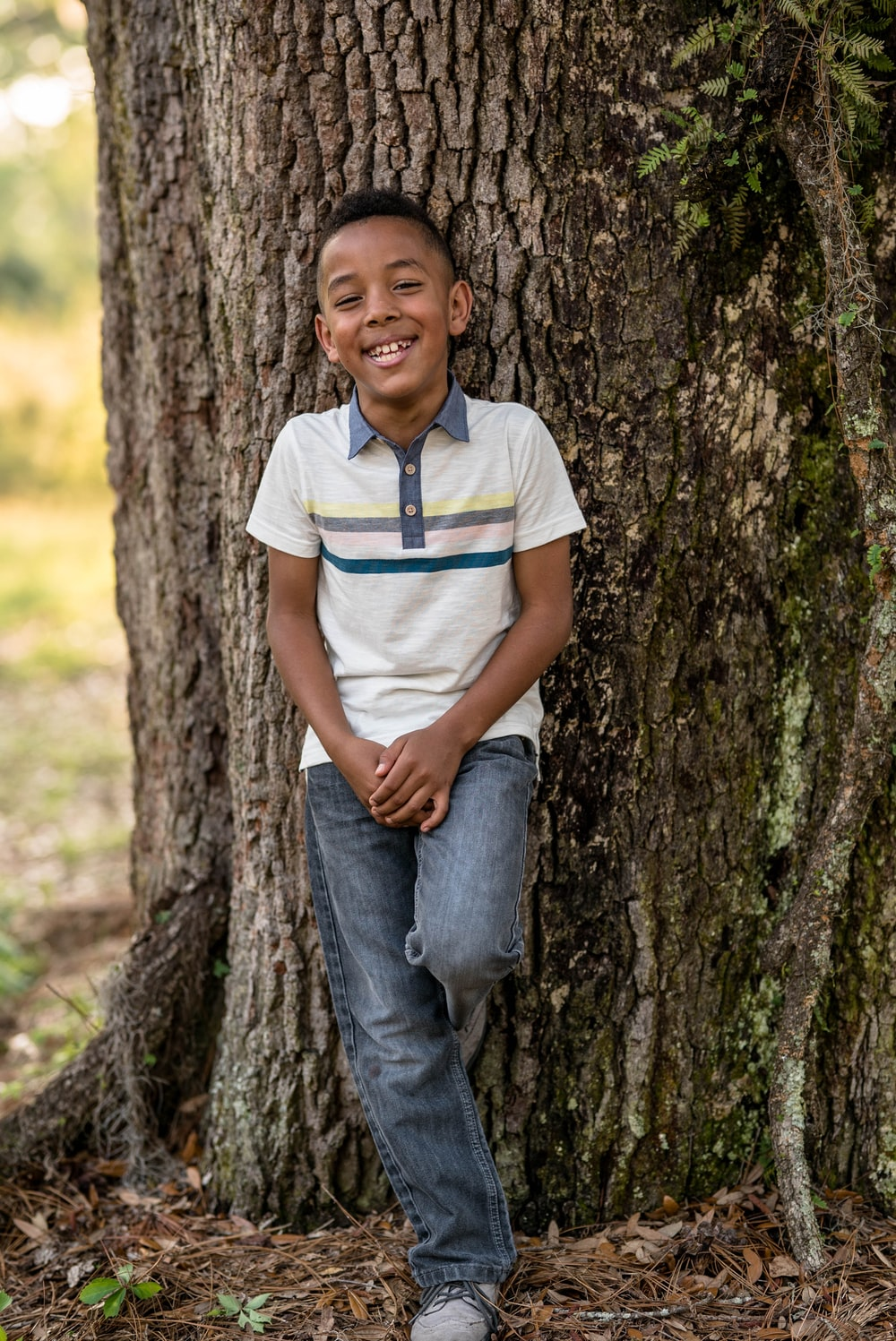 smiling boy leaning on tree during daytime