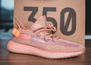 pair of pink Adidas Yeezy Boost 350 on brown wooden surface