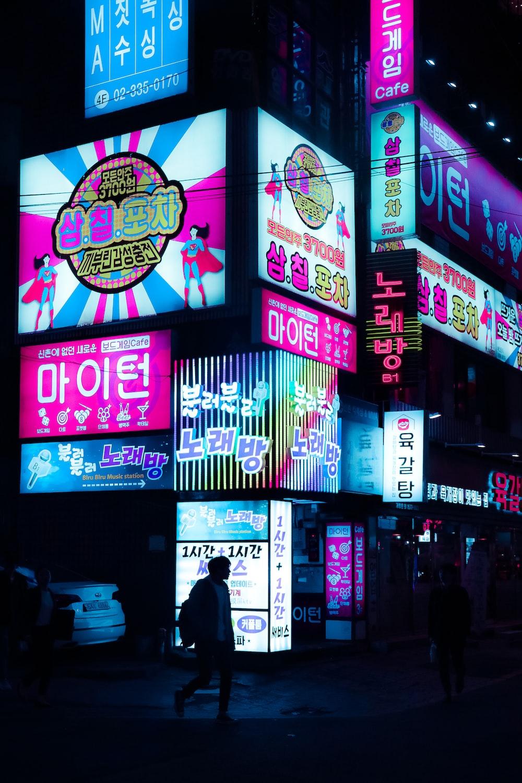 few people walking on street near buildings during night time
