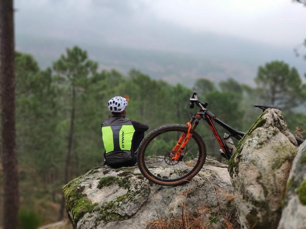 man on rock beside bicycle