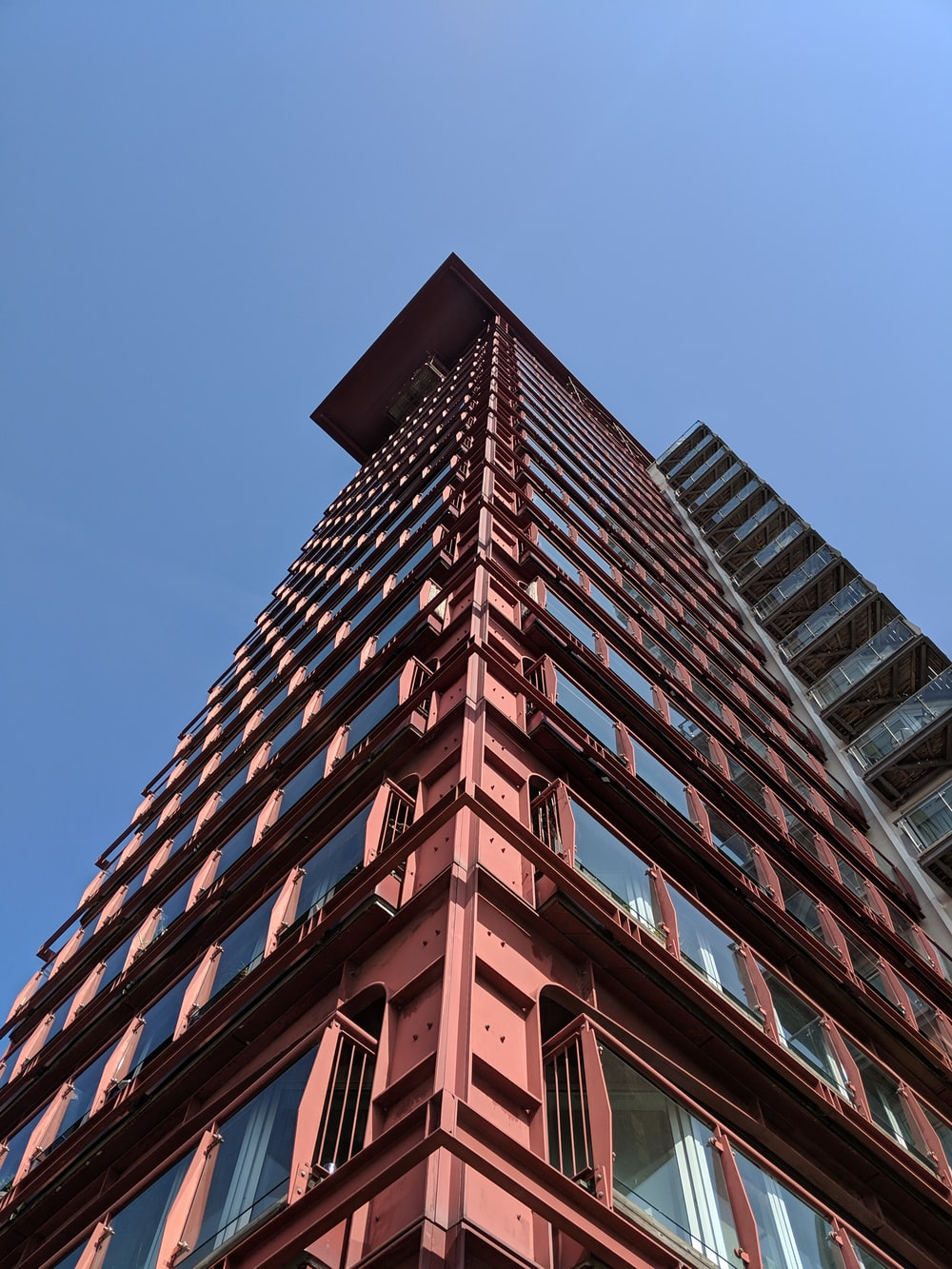 low angle photography of pink high-rise building