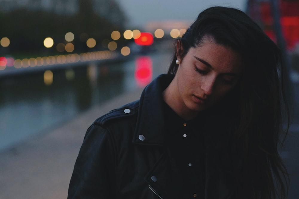 woman wearing black jacket standing near road