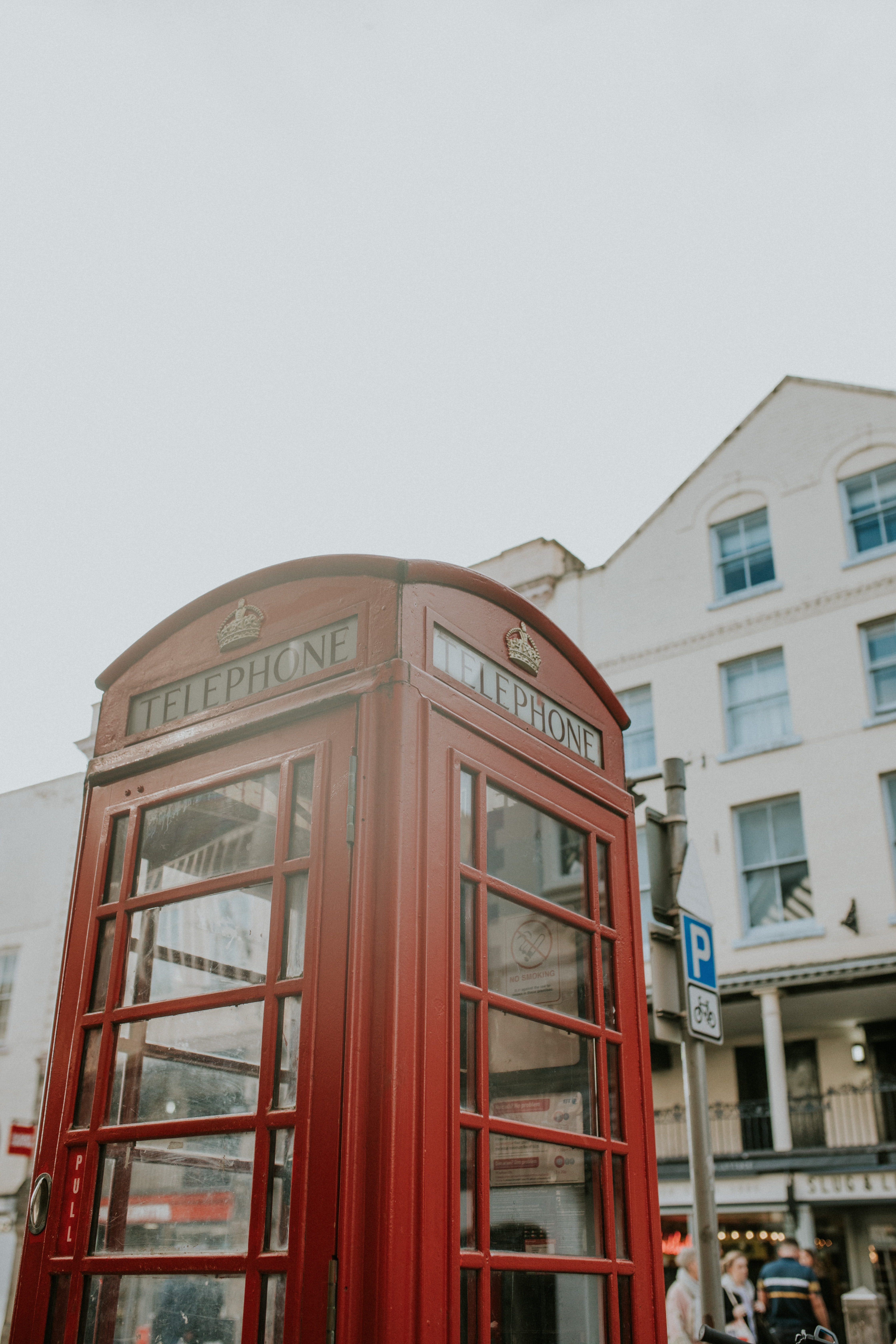red telephone booth near white concrete building