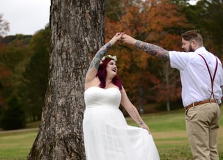 woman holding hand with man beside tree