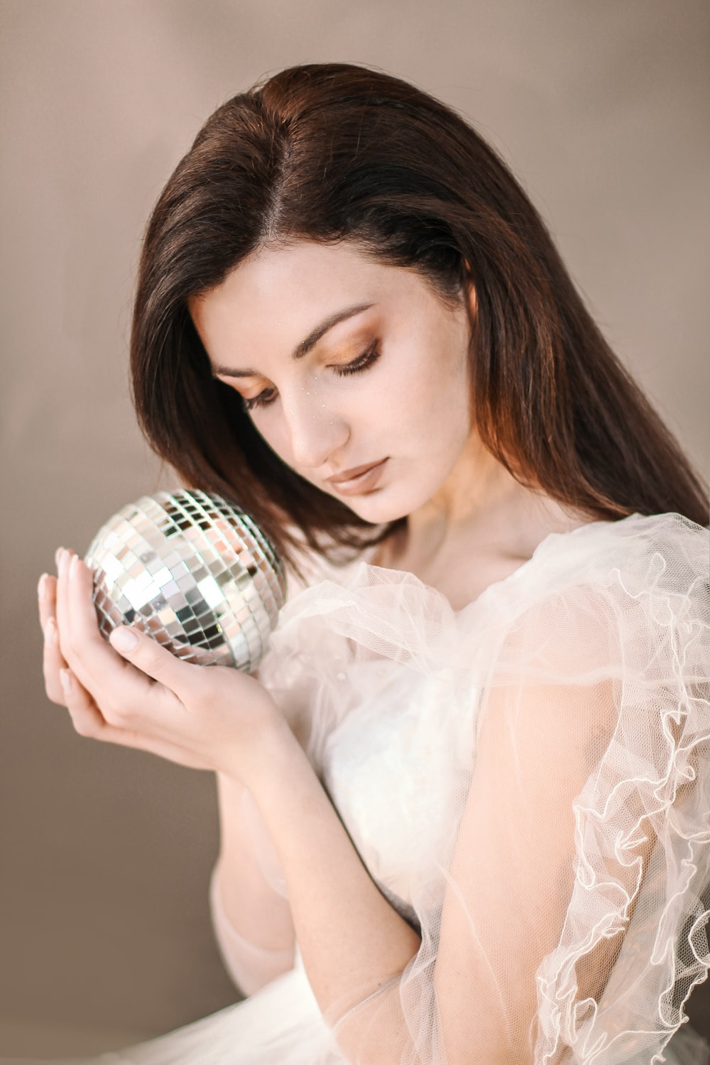 woman holding silver disco ball