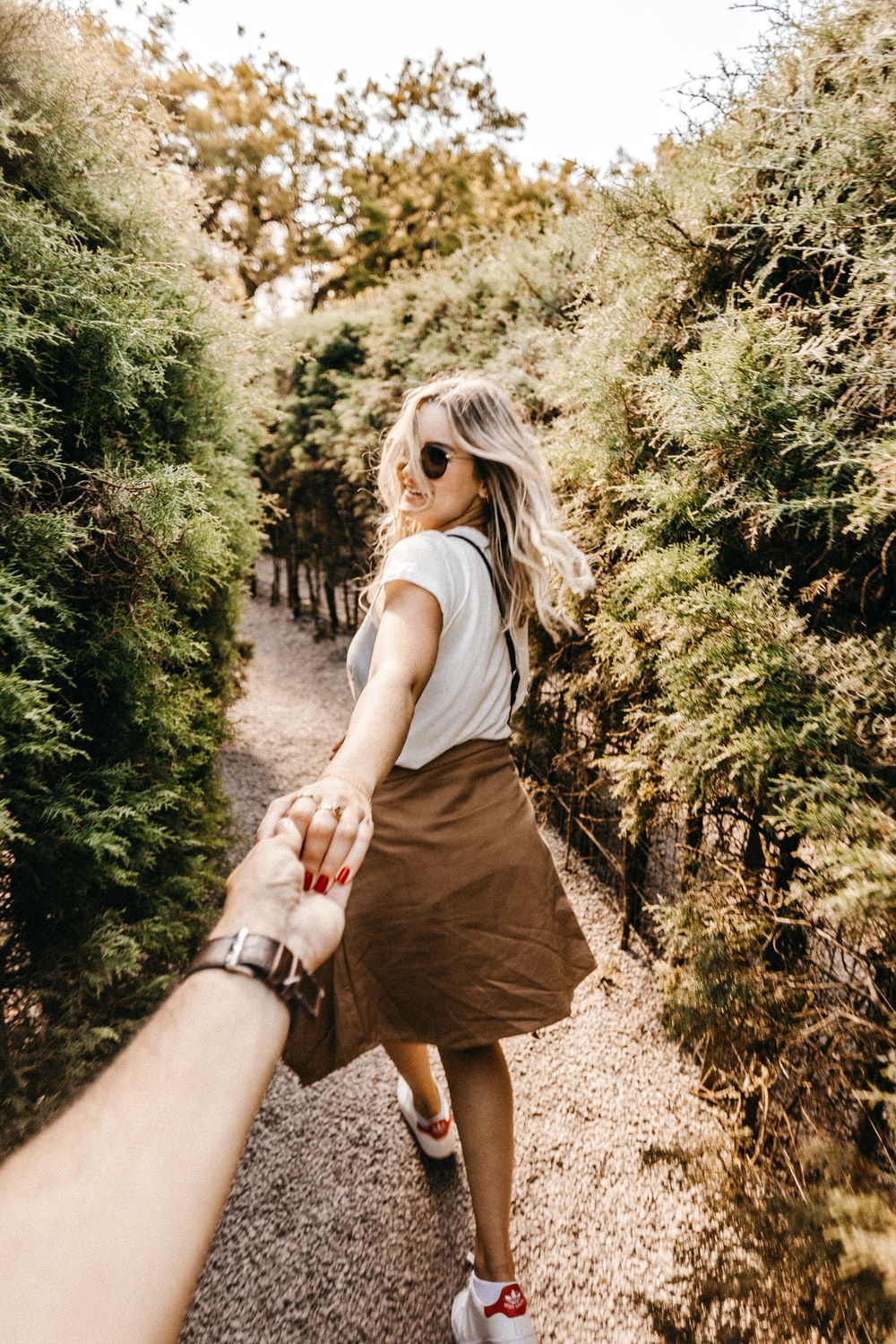 woman holding person's hand near trees
