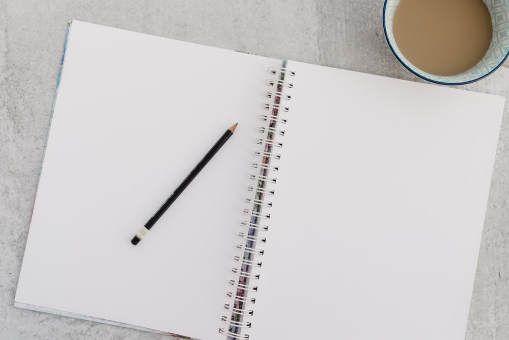 black pencil on white notebook