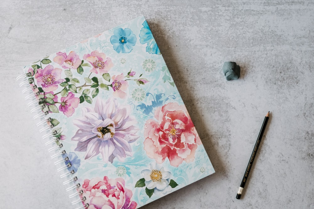 floral notebook beside pencil
