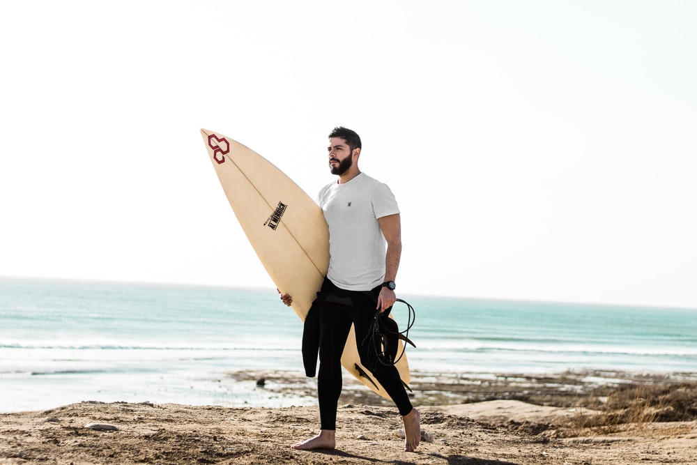 man walking at the sea while holding surfboard