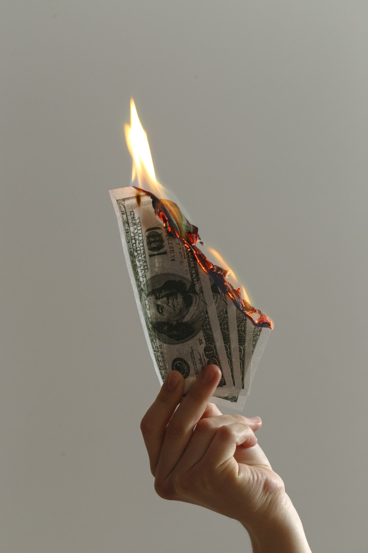 person holding lighted dollar bills