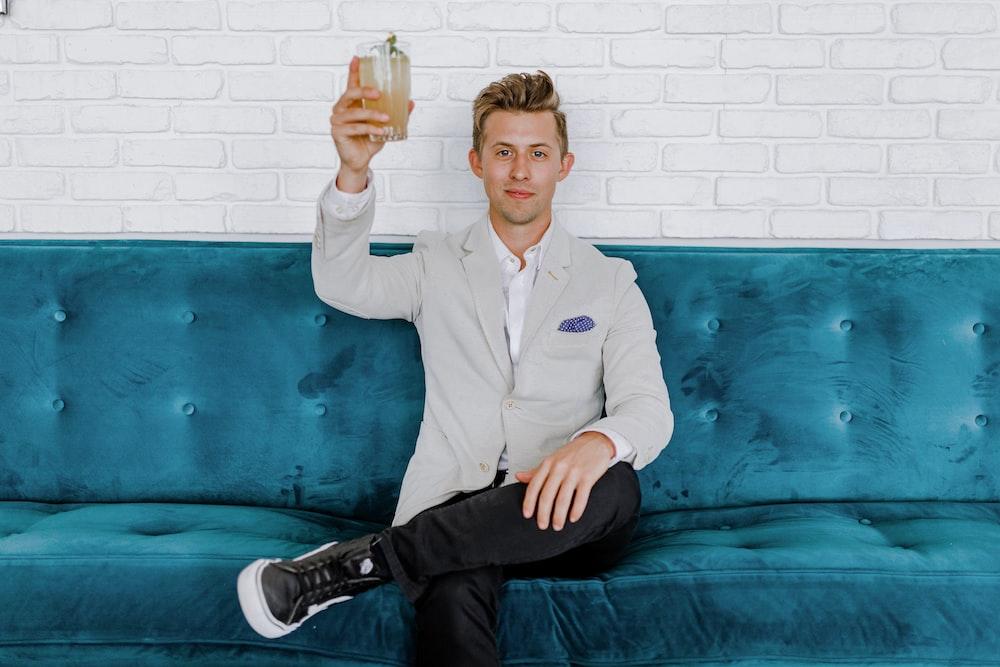 man in gray blazer raising drinking glass while sitting on sofa