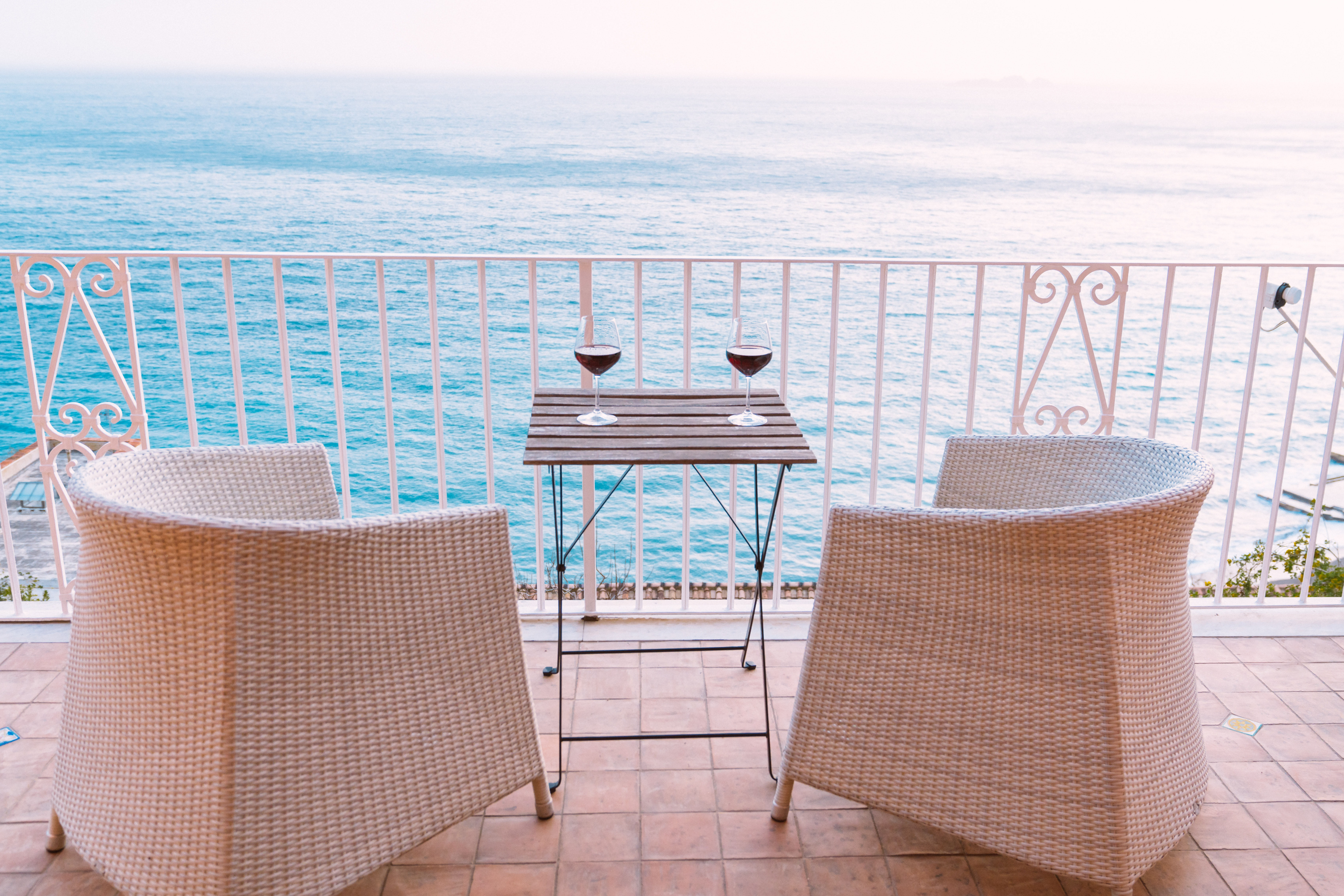 two white wicker chairs in front of blue sea